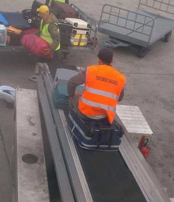 En photo-Aéroport de Tunis-Carthage : Un agent assis sur la valise de l'un des voyageurs